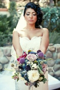 I love these colorful bouqets with traditional and non-traditional wedding flowers and feathers :)