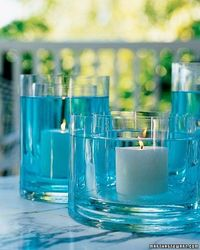 Two glass vases and tinted water can be combined to create a unique and festive effect on an outdoor table.